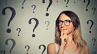 woman with glasses looking up at question marks
