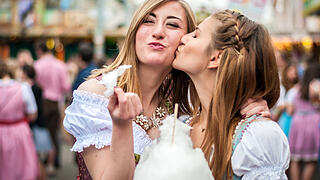 Two young women in Dirndl dress or tracht, kissing with